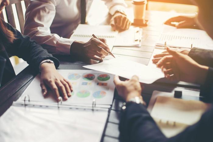 mesa de reuniões com mãos e papéis